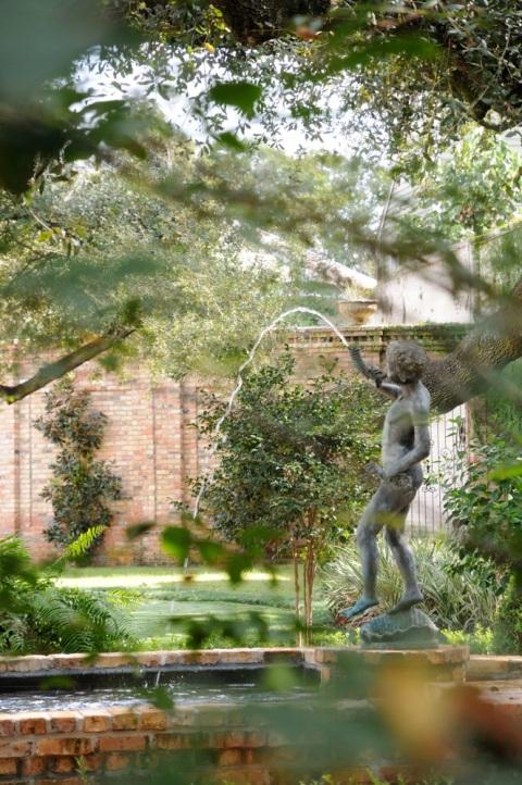 Peek through a gate at a sculptural fountain