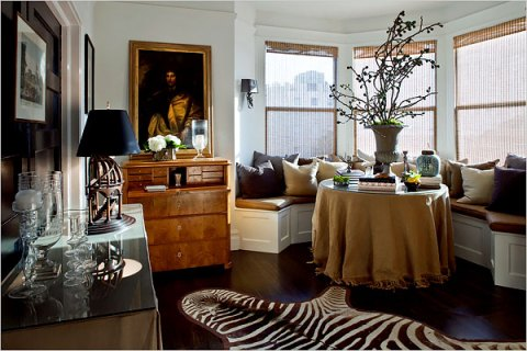 A custom built banquette makes a cosy dining area. If I'm not mistaken is that a burlap tablecloth from Ballard Designs?