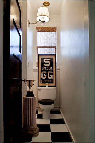 Classical lines even in a tiny powder room. The silver loving cup hides the T.P.